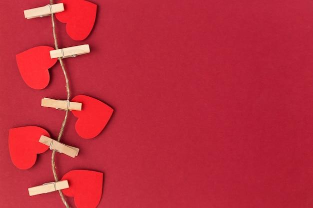 Cartão de dia dos namorados vermelho com corações vermelhos em prendedores de roupa.