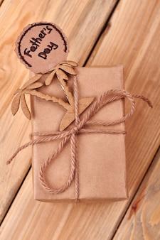 Cartão de dia dos pais e palmas das mãos. laço de corda na caixa de presente. viagem a países exóticos.