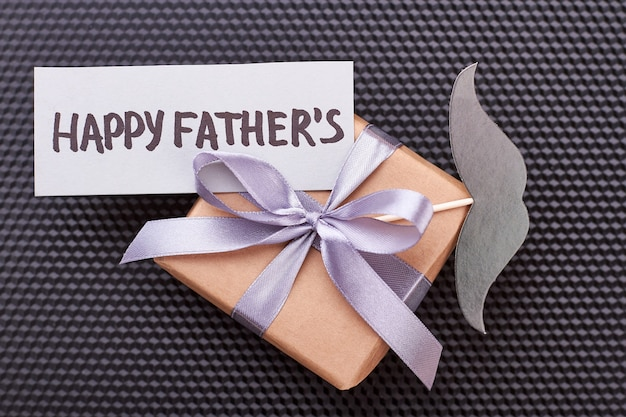 Cartão de dia dos pais no presente. bigode, caixa de presente, fundo preto. o pai ficará feliz.