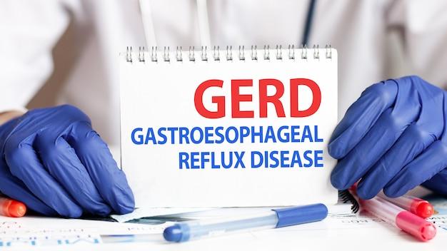 Cartão de drge nas mãos do médico. mãos de médico em luvas azuis segurando uma folha de papel com o texto gerd - abreviação de doença do refluxo gastroesofágico, conceito médico.