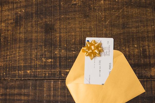 Cartão de embarque em envelope de presente com laço de fita sobre papel de parede texturizado