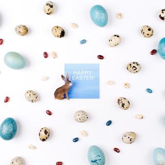 Cartão de ester feliz. layout criativo feito de codorna e ovos de páscoa azuis, coelho e doces em fundo branco. camada plana, vista superior. conceito de páscoa.