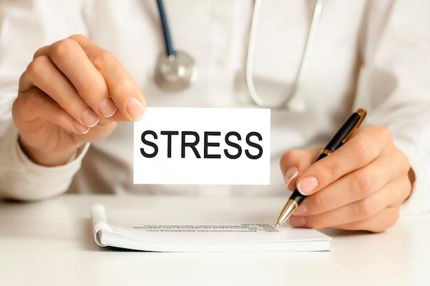 Cartão de estresse nas mãos do médico. o médico entrega uma folha de papel com estresse de texto, conceito médico.