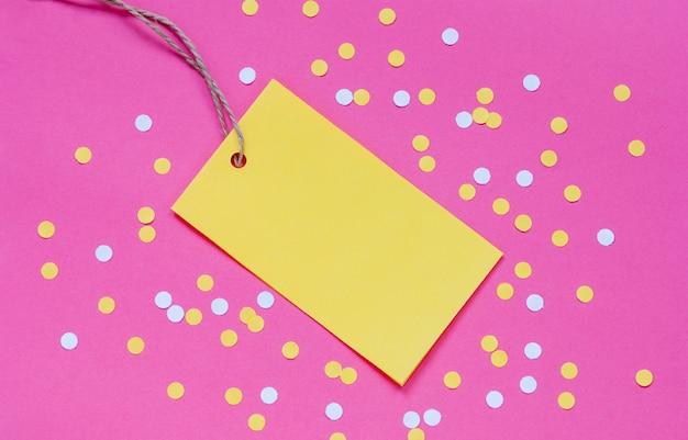 Cartão de etiqueta de papel amarelo e confetes em fundo rosa, lugar para logotipo, texto, desconto ou anúncio