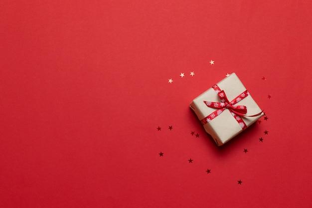 Cartão de felicitações com caixa de presente ou presente, confete na mesa vermelha