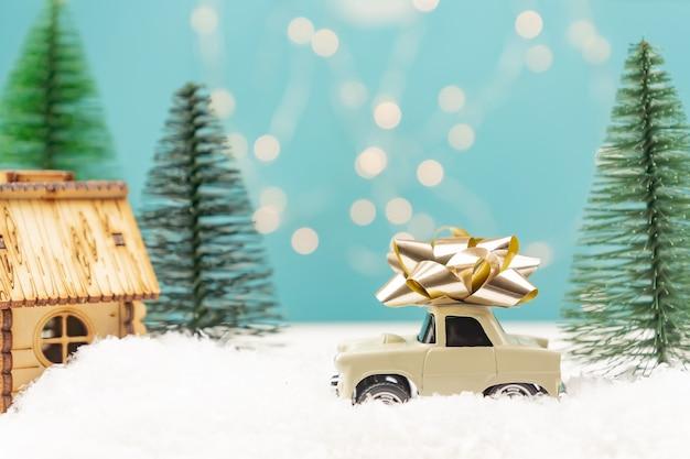 Cartão de felicitações de natal ou ano novo com carrinho de brinquedo vermelho, miniatura da árvore de natal e luzes de natal