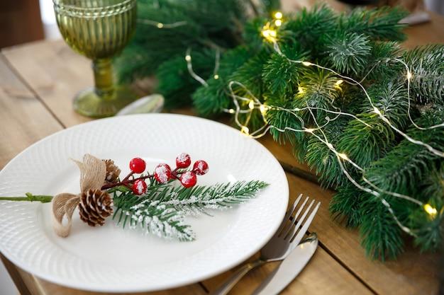 Cartão de felicitações. mesa de madeira com decoração de natal. configuração de mesa com utensílios. decoração festiva de ramos de abeto e guirlandas.