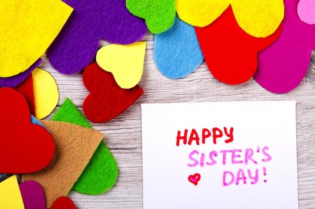 Cartão de felicitações no dia da irmã. corações brilhantes em fundo de madeira. parabenize sua irmã. relacionamentos familiares calorosos.