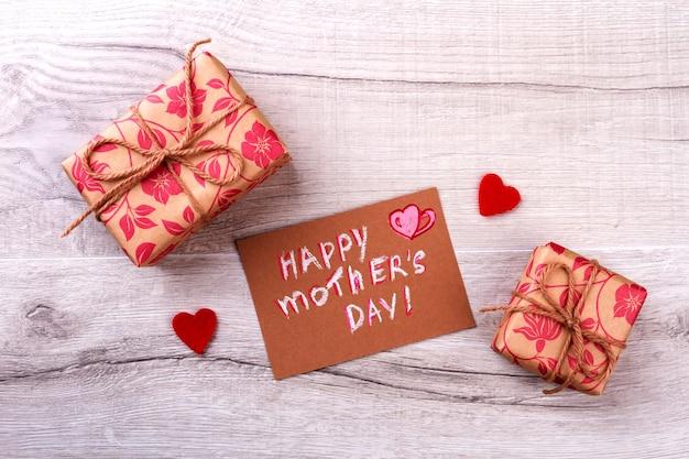 Cartão de felicitações no dia das mães. corações em tecido e presentes embrulhados. compartilhe o amor com a mãe. traga o clima de férias.