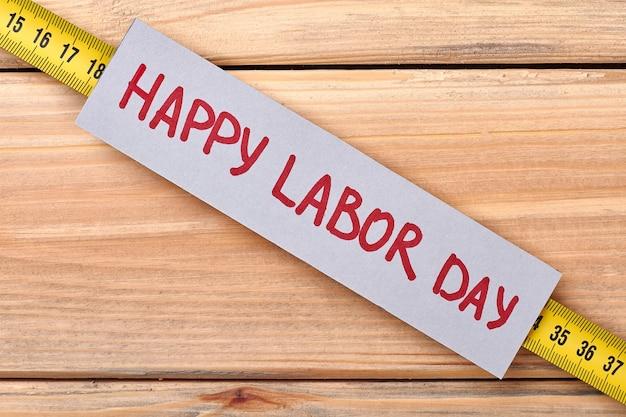 Cartão de felicitações no dia do trabalho. fita métrica e cartão postal. espalhe amor pelo trabalho.