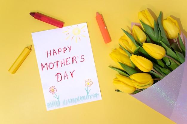Cartão de felicitações para a mãe no dia das mães, giz de cera colorido e tulipas amarelas sobre amarelo