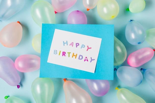 Cartão de feliz aniversário em balões contra o pano de fundo azul