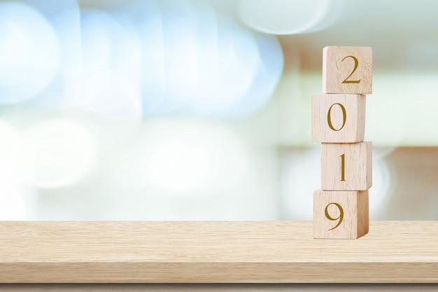 Cartão de feliz ano novo de 2019, cubos de madeira com 2019 sobre fundo de bokeh borrão Foto Premium