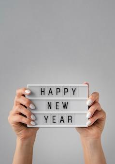 Cartão de feliz ano novo, sendo realizada nas mãos com espaço de cópia