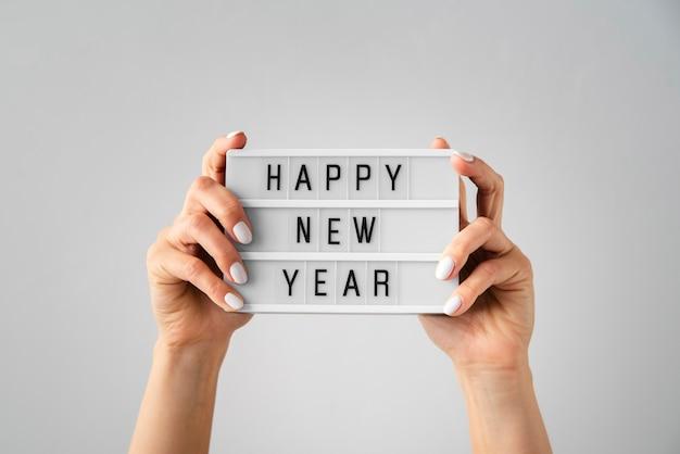 Cartão de feliz ano novo, sendo realizada nas mãos