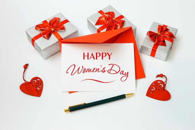 Cartão de feliz dia da mulher com envelope vermelho e presentes em fundo branco, 8 de março