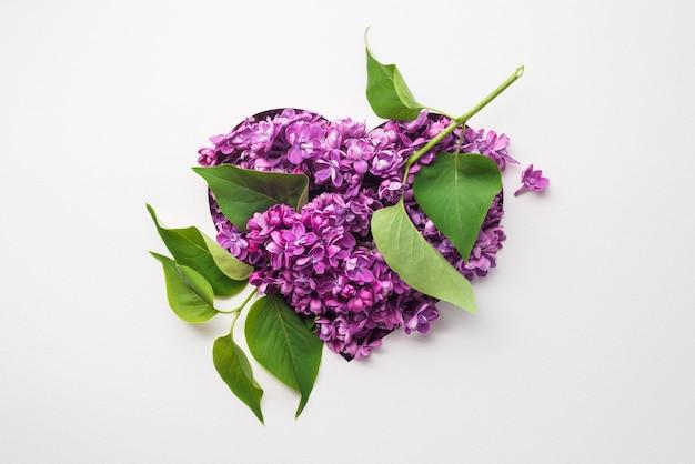 Cartão de feliz dia dos namorados com um coração floral de flores lilás em um fundo branco