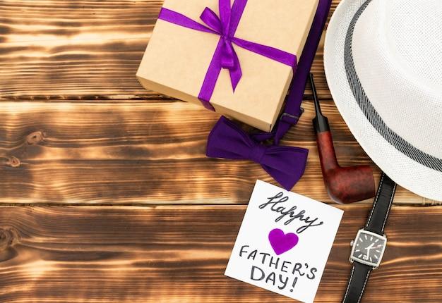 Cartão de feliz dia dos pais com caixa de presente, gravata, relógio de pulso, um chapéu e um cachimbo com fundo de madeira