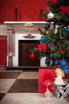 Cartão de feliz natal com um anjo na frente e uma lareira no fundo sensasional vintage natal interior estúdio tiro
