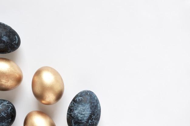Cartão de feliz páscoa moldura com ovos de páscoa de ouro e azuis. copie o espaço para texto. vista do topo.