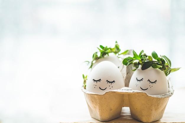 Cartão de feliz páscoa. ovos de páscoa fofos com um rosto pintado em uma coroa de flores de primavera