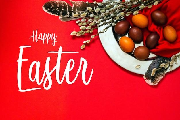 Cartão de feliz páscoa. ovos de páscoa vermelhos bonitos com penas e focas de salgueiro em chapa de ferro. feliz páscoa.