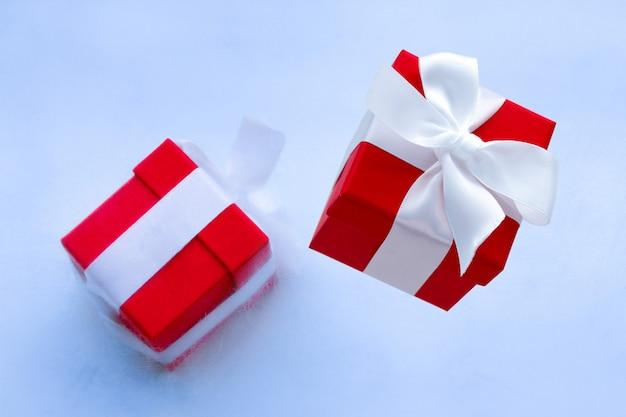 Cartão de férias de inverno ou cartaz de venda com caixa de presente congelada no gelo e caixa de presente vermelha com fita de cetim branca festiva com laço