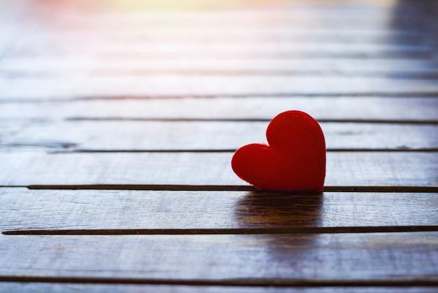 Cartão de férias dia dos namorados coração vermelho em madeira velha com pôr do sol para o conceito de filantropia - corações em um fundo de madeira doam ajuda dar amor cuidar
