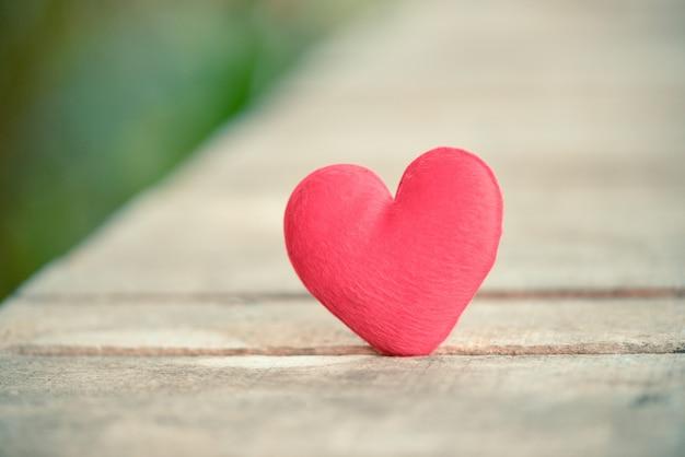 Cartão de férias dia dos namorados coração vermelho na madeira velha para o conceito de filantropia - os corações em um fundo de madeira doam ajuda dão amor cuidar