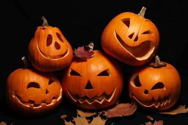 Cartão de férias para o halloween com abóboras de lanterna de jack e folhas de bordo laranja
