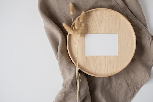 Cartão de folha de papel em branco com cauda de coelho no caixão de madeira e cobertor de linho cinza