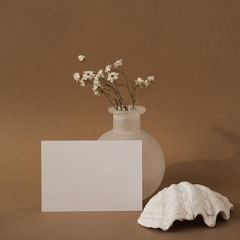 Cartão de folha de papel em branco com concha, lindas flores brancas contra parede marrom neutra.
