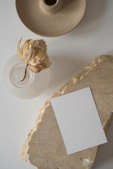 Cartão de folha de papel em branco com espaço de cópia de maquete, flor seca, pedra de mármore