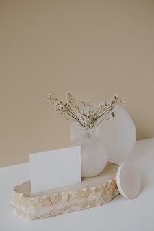 Cartão de folha de papel em branco com espaço de cópia de maquete, flores secas, pedra de mármore contra uma parede bege neutra.