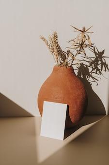 Cartão de folha de papel em branco com espaço de cópia e pote de barro com buquê de trigo seco com sombra de luz solar em branco