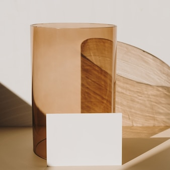 Cartão de folha de papel em branco com espaço de cópia e vaso de vidro bege com sombra de luz solar em branco