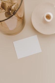 Cartão de folha de papel em branco com espaço de cópia, ramo de eucalipto em vaso de vidro em bege