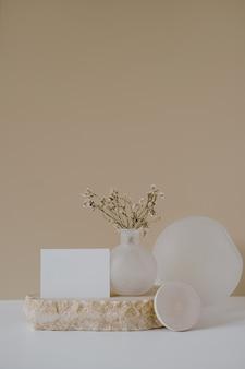 Cartão de folha de papel em branco com flores em pedra de mármore contra uma parede bege neutra