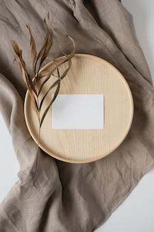 Cartão de folha de papel em branco com flores secas em caixão de madeira e cobertor de linho cinza