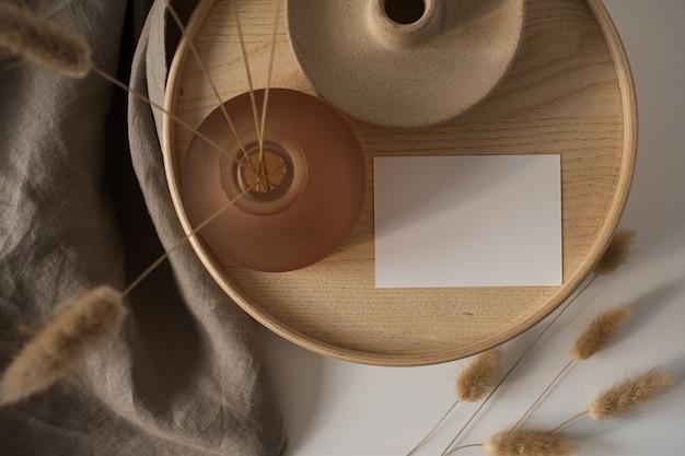 Cartão de folha de papel em branco com grama rabo de coelho em caixão de madeira e cobertor de linho cinza
