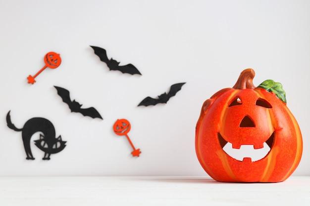 Cartão de halloween com abóbora ou jack-o-latern, gato preto e morcegos no fundo. foco seletivo.