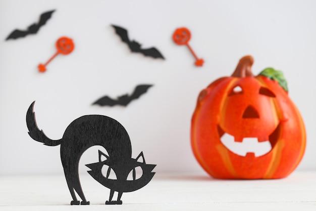Cartão de halloween com gato preto, jack-o-latern e morcegos. foco seletivo