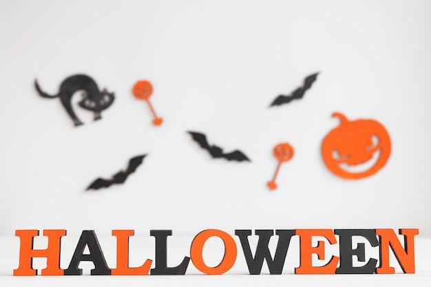 Cartão de halloween com letras laranja e pretas halloween gato preto jackolatern e morcegos