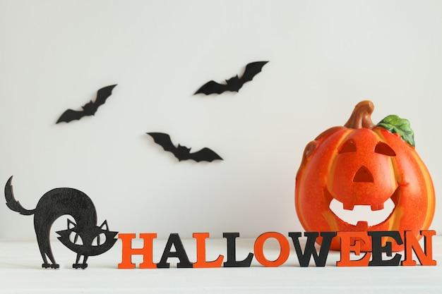 Cartão de halloween com letras laranja e pretas halloween jackolatern gato preto e morcegos