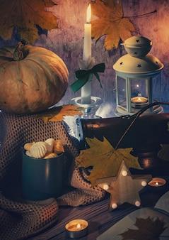 Cartão de halloween, fotografia vertical, abóbora, velas acesas e doces, fundo escuro.