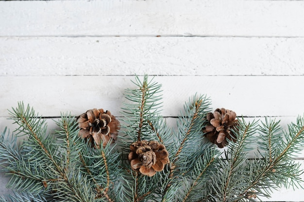 Cartão de inverno com galhos de pinheiro, cones, espaço de cópia de madeira branca, feriado de comemoração