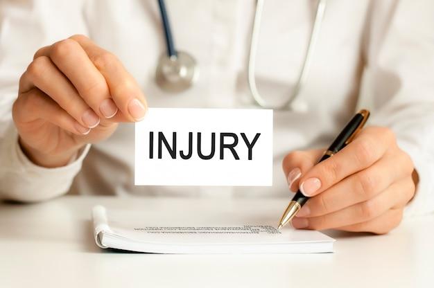 Cartão de lesão nas mãos do médico. o médico entrega uma folha de papel com o texto agonia, conceito médico.