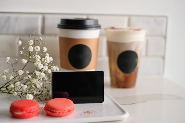 Cartão de maquete preto com a xícara de café e macaron