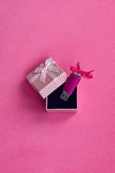 Cartão de memória flash usb rosa brilhante com um laço rosa encontra-se em uma pequena caixa de presente