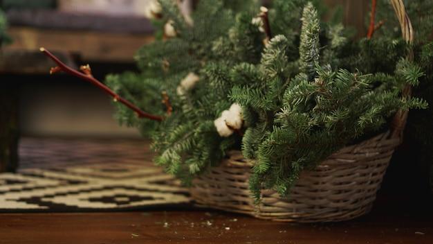 Cartão de natal - cesta com galhos de árvores de natal verdes
